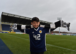 Pictured: 9 year old Joshua Holt before the match at the Falkirk Stadium <br /> <br /> How many Scottish football fans promise themselves a trip to every senior football ground in the country sometime in their life? Probably the majority when they retire.  One such fan who decided to get that milestone ticked off early in his life is nine year old Joshua Holt, from Edinburgh and an Edinburgh City fan, who completed his tour on Saturday 30 December at the Falkirk Stadium when Queen of the South are the visitors.  It has taken four years for Joshua, accompanied by his father Kenny, to complete the tour which started off on 31 August 2013 at Ibrox when Rangers took on East Fife.  A goal feast was on offer that day as Rangers won 5-0 but Joshua, like most five year olds, was more interested in everything else that accompanies a trip to one of the biggest stadiums in the UK.  His father, however, noticed a lot more than the football on the pitch; he had discovered what his football had been missing – a like minded companion.  This was their 'thing' to do together; father and son; come rain or shine.  Not the 'quality time' so often quoted as an essential for a parent but real time doing something they both enjoy.  A shared experience can build stronger bonds than any amount of treats from father to son.  They have travelled over five and a half thousand miles on their long journey and have enjoyed an average 2.9 goals per game.  Not a bad return for the commitment they have shown.<br /> <br /> Fans on match days have their own rituals, be it their lucky scarf; same bus for away games; or heading to the same seat for home games.  Joshua and Kenny go for the four Ps; popcorn, pin badge, programme and pie.  Popcorn for the trip to the ground with the programme and pin badges bought from the club shop as a reminder of the visit.  The catering is always tested especially on these cold days.  For the record Joshua can't see past a Dunfermline pie but his dad prefers a Ross Cou