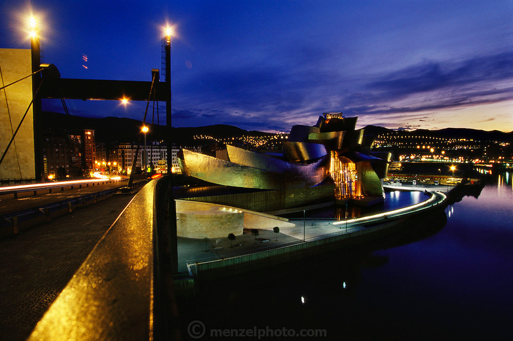 Early evening view of the Guggenheim Art Museum, Bilbao, Spain designed by architect Frank Gehry. Seen from bridge over the river.