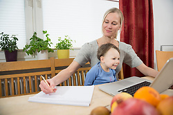 Mother and son using laptop while making notes, smiling