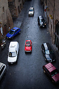 A red Fiat 500 drives down a cobblestone street in the historic quarter of Orvieto, Umbria, Italy.