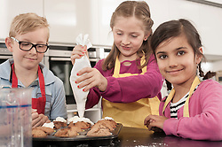 Schoolgirl icing on muffins with icing bag in home economics class, Bavaria, Germany
