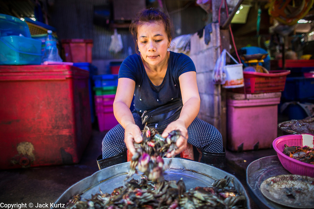 17 JANUARY 2013 - SAMUT SONGKHRAM, SAMUT SONGKHRAM, THAILAND: A market vendor in the Samut Songkhram market sets out crabs she's selling. Four trains each day make the round trip from Baan Laem, near Samut Sakhon, to Samut Songkhram, the train chugs through market eight times a day (coming and going). Each time market vendors pick up their merchandise and clear the track for the train, only to set up again when the train passes. The market on the train tracks has become a tourist attraction in this part of Thailand and many tourists stop to see the train on their way to or from the floating market in Damnoen Saduak.    PHOTO BY JACK KURTZ