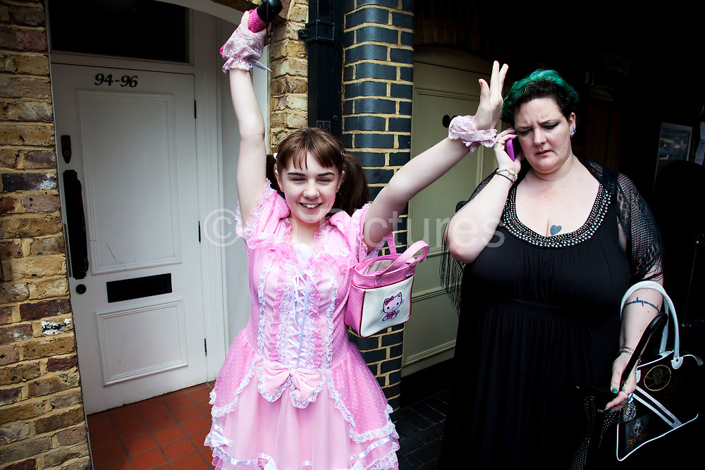 LONDON, ENGLAND, UK, JUNE 11TH 2011. Mother Louise Irwin-Ryan with her daughter Georgia (11, wearing a pink Lolita dress) spending a day out together in Camden Town, North London. Georgia is excited to be going to her favourite shop whilst Louise takes a call. Louise is on various benefits to help support her family income, and housing, although recent government changed to benefits may affect her family drastically, possibly meaning they may have to move out of London. Louise Ryan was born on the Wirral peninsula in 1970.  She moved to London with her family in 1980.  Having lived in both Manchester and Ireland, she now lives permanently in North London with her husband and two children. Through the years Louise has battled to recover from a serious motorcycle accident in 1992 and has recently been diagnosed with Bipolar Affective Disorder. (Photo by Mike Kemp/For The Washington Post)