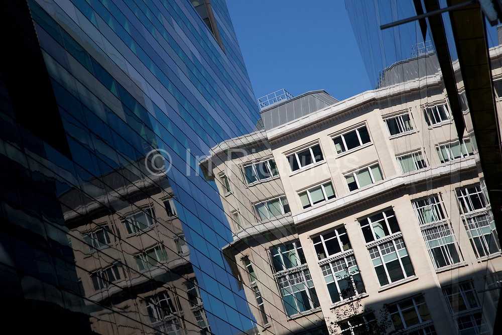 Old architecture relected in the new in the City of London, where modern money rivals for space with older tradition. UK.