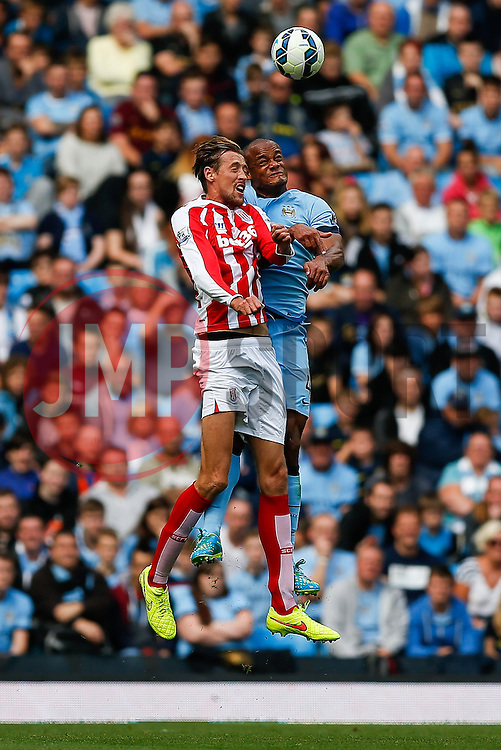 Peter Crouch of Stoke and Vincent Kompany of Manchester City compete in the air - Photo mandatory by-line: Rogan Thomson/JMP - 07966 386802 - 30/08/2014 - SPORT - FOOTBALL - Manchester, England - Etihad Stadium - Manchester City v Stoke City - Barclays Premier League.