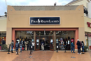 People stand in line outside the Polo Ralph Lauren store the day before Christmas at the Citadel Outles amid the global coronavirus COVID-19 pandemic, Thursday, Dec. 24, 2020, in Los Angeles.