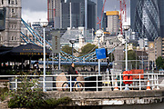 With a background of the capital's financial district and the northern bascule of Tower Bridge, Londoners walk along Butler's Wharf on 20th October 2021, in London, England.