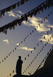 Asia, Nepal, Kathmandu, Buddhist monk praying beneath lines of prayer flags at Bodhnath Stupa at dusk