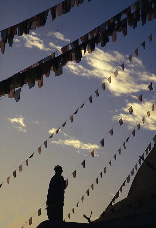 Asia, Nepal, Kathmandu, Buddhist monk praying beneath lines of prayer flags at Bodhnath Stupa at dusk