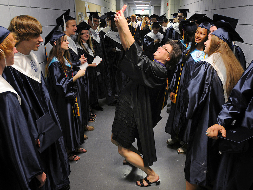 South Brunswick High School teacher Cathy Johnson pauses to take a selfie photo with graduates before the start of the graduation ceremonies at Odell Williamson Auditorium on the campus of Brunswick Community College in Bolivia, N.C., Saturday, June 14, 2014. Photo by Michael Cline Photography