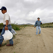 SAN DIEGO, CA, MAY 4, 2007:  Migrants who work the nearby fields or wait for work at day labor sites often use McGonigle Canyon in San Diego county as home. They construct living quarters out of branches, leaves and mud in the middle of a canyon lined with modern homes. Local activist Robert Baca, who runs a mobile health clinic for the migrants, talks to a migrant making his way to camp with provisions. (Photo by Todd Bigelow/Aurora) Please contact Todd Bigelow directly with your licensing requests.
