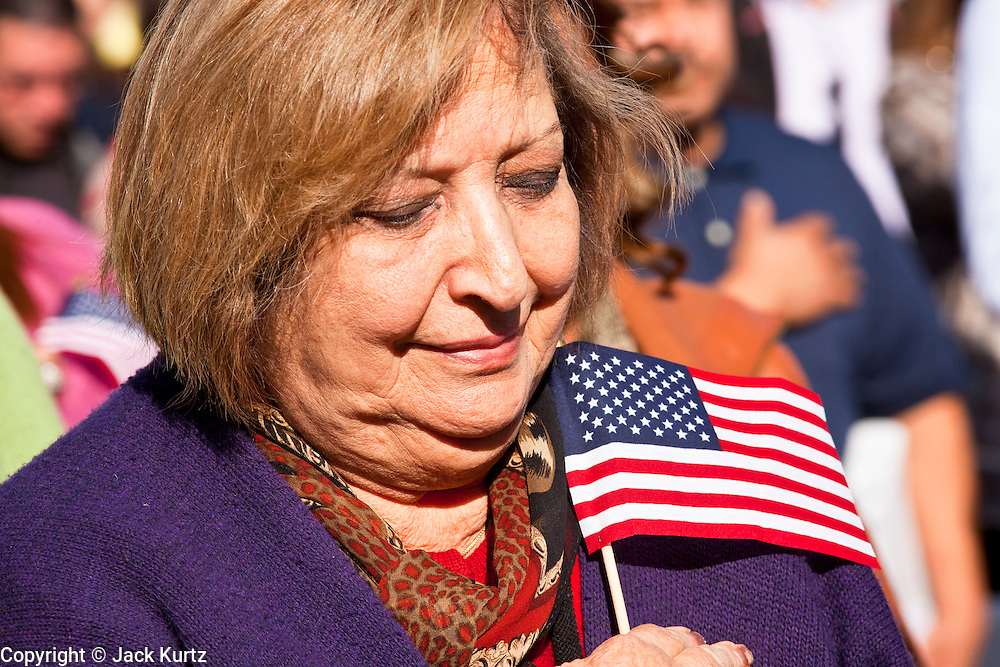 14 JANUARY 2012 - CHANDLER, AZ:    A woman being naturalized as a US citizen holds an American flag over her heart in Chandler, AZ, Jan. 14. More than 140 people from 21 countries were naturalized as United States citizens Saturday in Chandler. This is the third year Chandler has sponsored a naturalization ceremony in connection with the Dr. Martin Luther King holiday. PHOTO BY JACK KURTZ