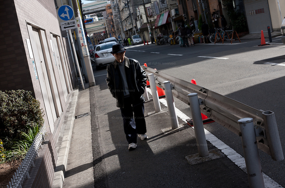A day labourer walking down a street in Kotobukicho. a slum area near ishikawacho in Yokohama that is home to Japan's  day labourers and some of the poorest peoiple in the country, Yokohama, Kanagawa, Japan. February 6th 2010