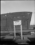 """Ackroyd 03295-01. """"West Coast Trans-Oceanic Steamship. Dock at Swan Island. Hiram Maxim."""" (Maxim is the ship) """"All photographs made Thursday, December Sixth 1951 by Everett F. Chandler and Hugh S. Ackroyd, of Ackroyd Photography Inc."""" """"Unsafe sign at bow of Hiram S. Maxim. One of several signs posted all along the outfitting dock."""""""