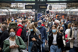© Licensed to London News Pictures. 10/07/2021. London, UK. Members of the public are seen wearing face masks as they disembark a train at Kings Cross Station in central London. Final lifting of Covid-19 regulations will take place on July 19th. Photo credit: Ben Cawthra/LNP