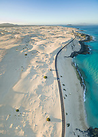 Aerial panoramic view of a car driving on the road in Corralejo Dunes Natural Park in Fuerteventura, Canary Islands.
