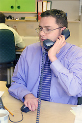 Man with disability; who is wheelchair user; using telephone in office,