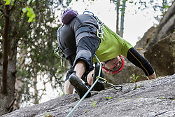 Male rock climber scaling a rock face at Oberried climbing garden, Otztal, Tyrol, Austria