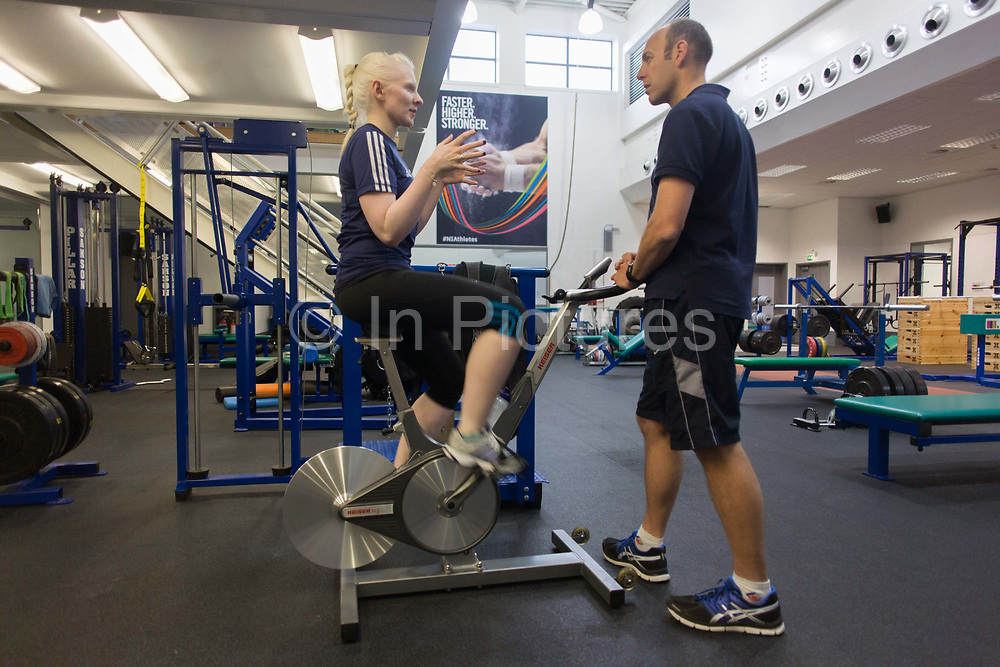 Partially-sighted skiing paralympian from the Sochi Olympics, Kelly Gallagher trains with her trainer in the gym at the Sports Institute, University of Ulster, Northern Ireland, UK. Consulting with her trainer she talks about a new training regime for the forthcoming winter season. <br /> Kelly Marie Gallagher, MBE is a Northern Irish skier and the first athlete from Northern Ireland to compete in the Winter Paralympics. Gallagher won Britain's first ever Winter Paralympic gold medal during Sochi 2014.