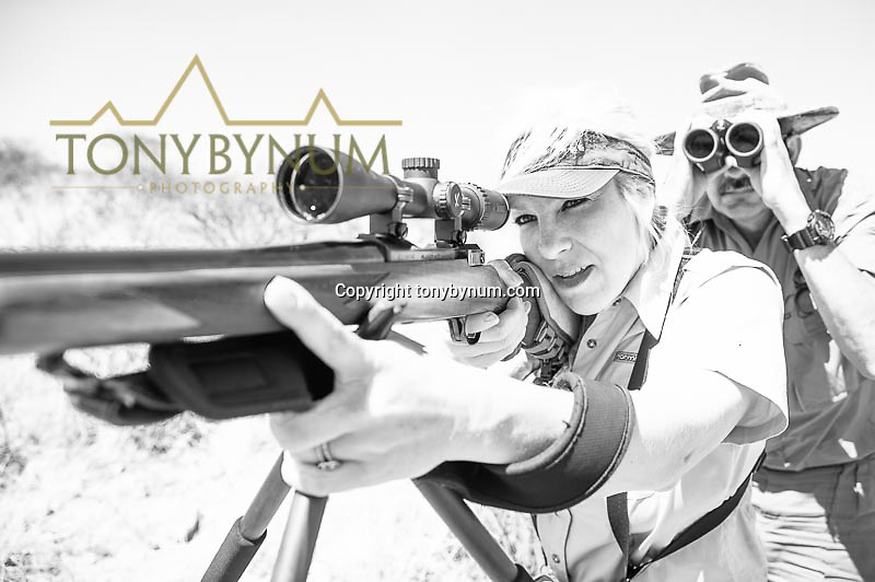 woman looking though rifle scope ready to shoot hunting photograph