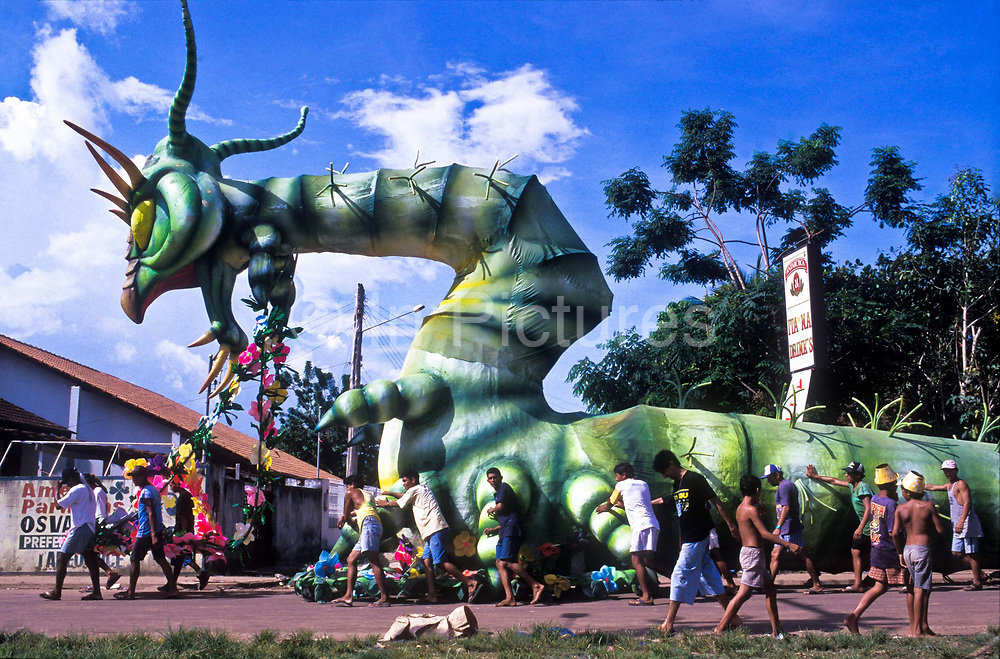 """A large oversized Caterpiller leaves the warehouse to enter the """"Bumbodromo"""", the stadium where the """"Boi Bumba"""" Carnival takes place, Parintins, Brazil"""