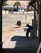 Local man sitting outside a salon in Swakopmund, Namibia