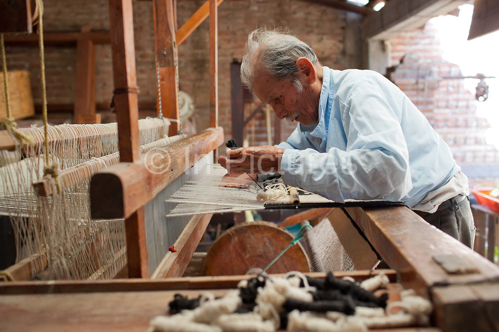 A man weaving wool on a loom in the traditional way. Oaxaca in southern Mexico is known for its artisan communities, with each valley having a different specialism - weaving, pottery, wood carving.