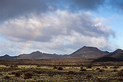 A rainbow appears above volcanic peaks on 27th November 2020 in Los Volcanes Natural Park in Lanzarote, Spain. The island was transformed by huge volcanic eruptions from 1731-36, which give it its unique dramatic landscape...