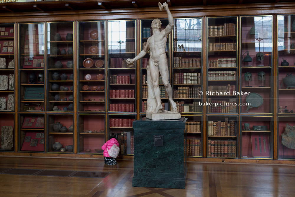 A young visitor inspects classical literature near the the sculpture of Rondanini's Faun - a 2nd century Roman copy of a Greek original - in the Enlightenment Gallery of the British Museum, on 11th April 2018, in London, England.