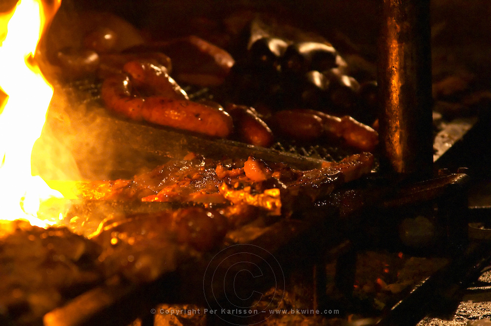 The restaurant kitchen with a big grill barbecue where all sorts of pork beef and chicken meat and sausages are grilled. Close-up of some sausages and meat pieces on the grill, with fire. at the restaurant La Estacada on the waterside Montevideo, Uruguay, South America