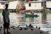 04 JANUARY 2012 - BANGKOK, THAILAND:  A man paddles his canoe past another man who is making merit by feeding pigeons at Wat Mahabut in eastern Bangkok. The temple was built in 1762 and predates the founding of the city of Bangkok. Just a few minutes from downtown Bangkok, the neighborhoods around Wat Mahabut are interlaced with canals and still resemble the Bangkok of 60 years ago. Wat Mahabut is a large temple off Sukhumvit Soi 77. The temple is the site of many shrines to Thai ghosts. Many fortune tellers also work on the temple's grounds.   PHOTO BY JACK KURTZ