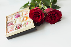 Chocolate truffle and roses on table, close up