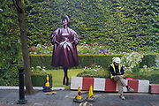 Hoarding outside a shop under refurbishment makes an interesting street scene as a fashion model poses next to a worker taking a break on New Bond Street in London, England, United Kingdom. A weird visual juxtaposition is created as people integrate with the large scale printed photograph of a countryside garden.