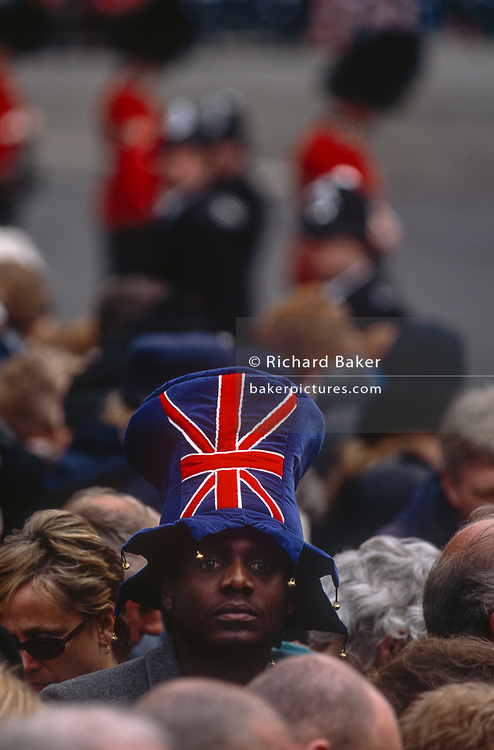 During the slow wait to view the lying in state of the recently-deceased Queen Mother in Westminster, one royalist and patriot in the queue wears a Union Jack hat, on 5th April 2002, in Lonon, England.