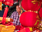 "18 JANUARY 2017 - BANGKOK, THAILAND: A vendor who sells Chinese New Year lanterns waits for customers in Bangkok's Chinatown district. Chinese New Year, also called Lunar New Year or Tet (in Vietnamese communities) starts Saturday, 28 January. The coming year will be the ""Year of the Rooster."" Thailand has the largest overseas Chinese population in the world; about 14 percent of Thais are of Chinese ancestry and some Chinese holidays, especially Chinese New Year, are widely celebrated in Thailand.      PHOTO BY JACK KURTZ"