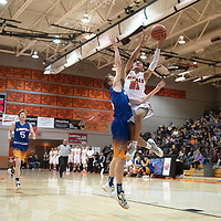 Gallup Bengal Jeffrey Yazzie (21) is fouled by Bloomfield Bobcat Zach Boehm (4) as he drives to the basket for a layup Friday night at Gallup High School in Gallup. The Bengals took the win 78-56.