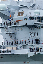 © Licensed to London News Pictures. 16/11/2019. Portsmouth, UK.  Crew aboard HMS Prince of Wales, the Royal Navy's second Queen Elizabeth-class aircraft carrier, as she sails into Portsmouth Naval Base for the first time this afternoon, 16th November 2019. The £3.1 billion warship has been undergoing eight weeks of sea trials in the Moray Firth. Photo credit: Rob Arnold/LNP