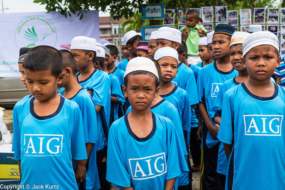 07 JULY 2013 - NARATHIWAT, NARATHIWAT, THAILAND:   Thai Muslim school boys wait to talk to Royal Thai Marines during a civilian outreach Sunday. Royal Thai Marines in Narathiwat province held a special ceremony Sunday in advance of Ramadan. They presented widows, orphans and indigent people with extra rice and food as a part of the Thai government's outreach to resolve the Muslim insurgency that has wracked southern Thailand since 2004. The Holy Month of Ramadan starts on about July 9 this year. Muslims are expected to fast from dawn to dusk, engage in extra prayers, recitation of the Quran and perform extra acts of charity during Ramadan. It is the holiest month of the year for Muslims.  PHOTO BY JACK KURTZ