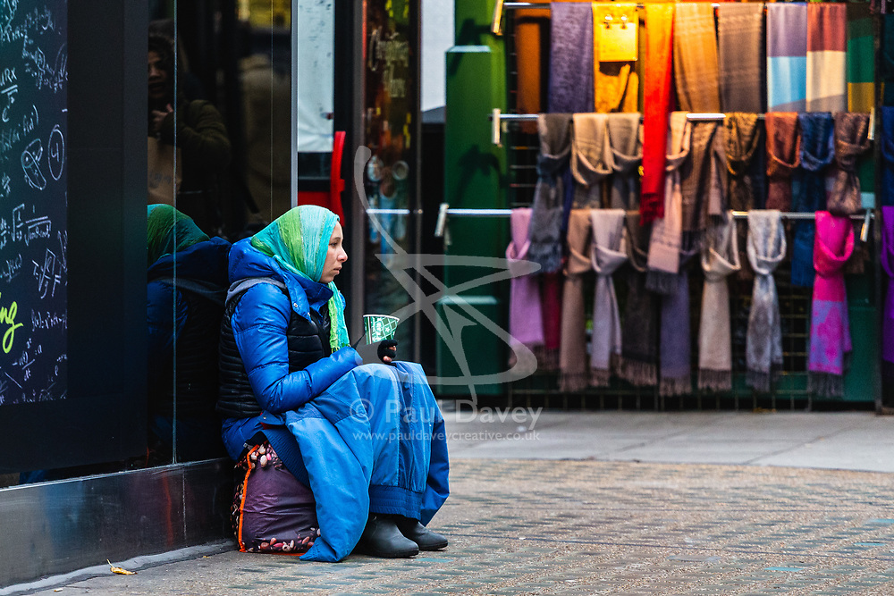 A woman in a headscarf begs on Oxford Street. Homeless Britons are coming under increasing pressure as a surge of Roma beggars from Romania arrive on the streets of London to take advantage of the generosity of Christmas shoppers. London, December 04 2018.