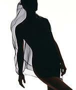 Graceful nude woman in silhouette wrapped in scarf against a white background