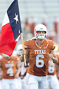 AUSTIN, TX - AUGUST 31: Case McCoy #6 of the Texas Longhorns carries the Texas flag onto the field before kickoff against the New Mexico State Aggies on August 31, 2013 at Darrell K Royal-Texas Memorial Stadium in Austin, Texas.  (Photo by Cooper Neill/Getty Images) *** Local Caption *** Case McCoy
