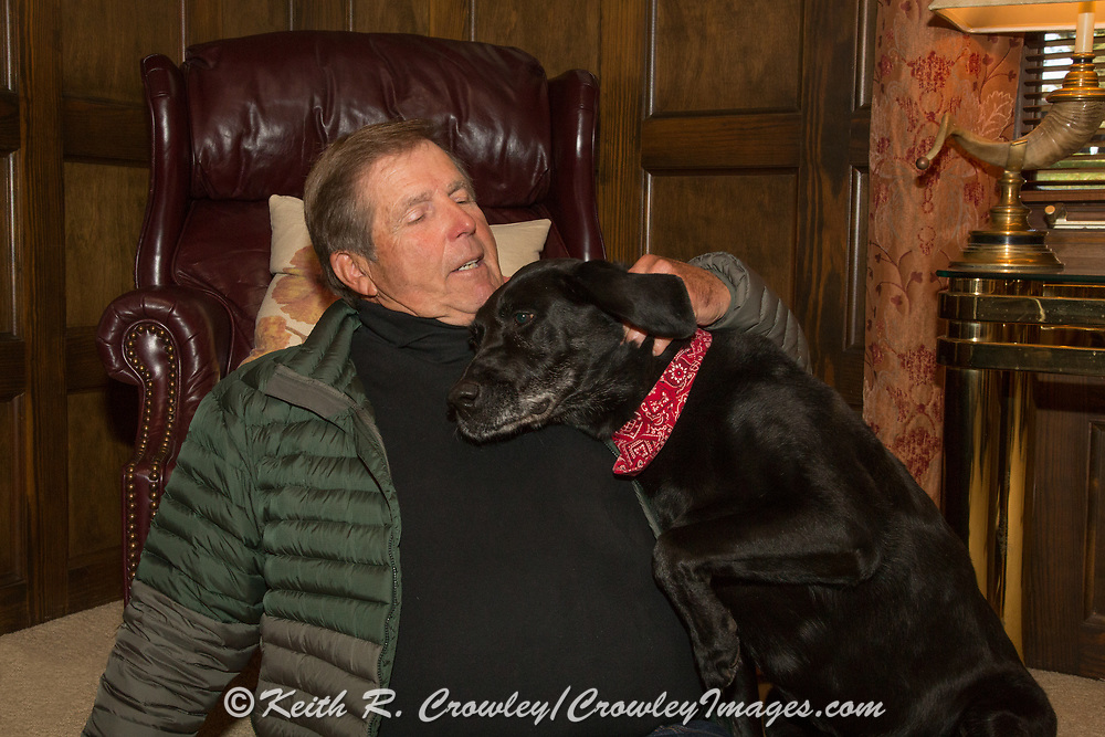 TV host and producer Ron Schara relaxes at home with his Black Lab Raven