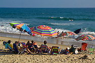 People under colorful shade umbrellas on sand beach in summer, Carlsbad, San Diego County coast, California