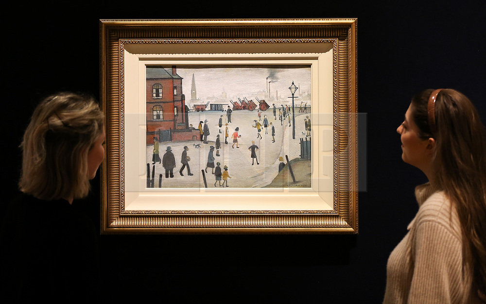 """© Licensed to London News Pictures. 12/11/2018. London, UK. Staff members looks at """"Rounders"""" oil on panel by Laurence Stephen Lowry R.A. (British, 1887-1976). (Estimate £400,000-600,000).<br /> Bonhams Modern British and Irish Art photocall. Auction to be held on 14 November 2018. Photo credit: Dinendra Haria/LNP"""