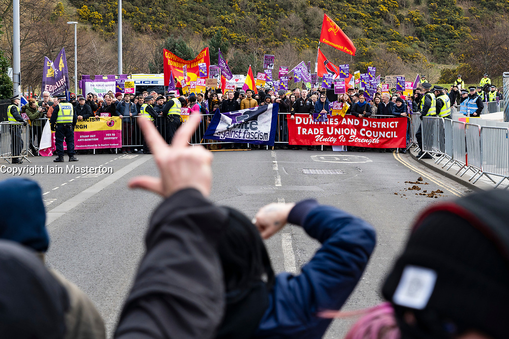 Edinburgh, Scotland, UK. 23 March, 2019. March to the Scottish Parliament in Edinburgh by far-right Scottish Defence League (SDL) was met by a counter demonstration by several left wing groups such as Unite Against Fascism, Muslin Women's Association and Edinburgh Antifa. A heavy police presence was in force and the SDL were closely escorted to and from Waverley Station. Pictured; SDL and anti-fascist protestors face off.