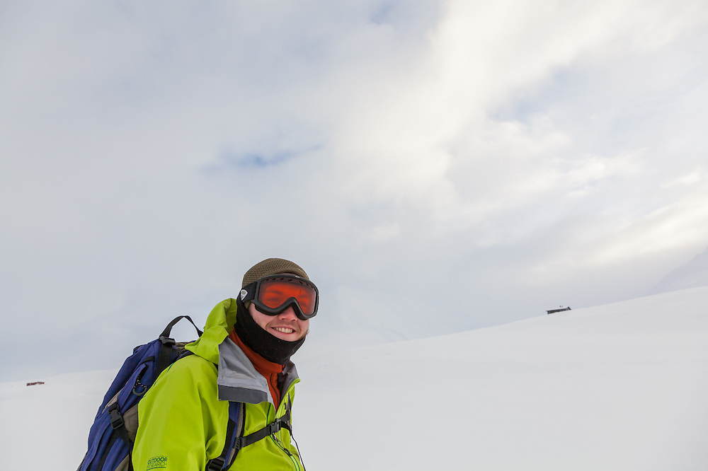 Nate Stevens grins in anticipation of great ski turns as he passes a couple backcountry cabins at the mouth of Foxdalen in Adventdalen, Svalbard.