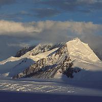 The sun sets on mountains above a glacier near Jones Sound on the Antarctic Peninsula, Antarctica.