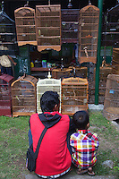 Indonesia man and his son shopping for birds at the Yogyakarta Bird Market - a popular attraction for visitors to Yogyakarta as well as aficionados of birds and exotic bird cages.  An endearing quality of Asian men who fondly take care of birds, walk them down the street as loving pet owners.