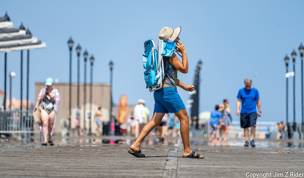 A young man talks on his cellphone as he arrives along the boardwalk.