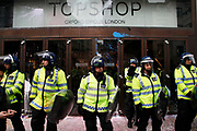 Police in riot gear protecting Topshop on Oxford Street. Anti capitalists / anarchists go on the rampage through central London on the back of the peaceful TUC protest march. The masked demonstrators ran a twisting route through the capital confusing the police and creating a situation which was very difficult to manage. The protesters attacked banks, shops and hotels, and the police in riot gear fought  face to face with them as they were pelted with ammonia, paint and fireworks loaded with coins.